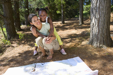 Mother and daughter looking at map in forest