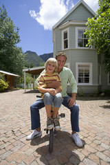 Father and son riding bicycle in patio