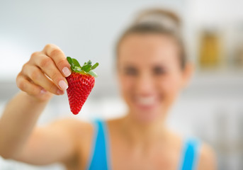 Closeup on happy young woman showing strawberry