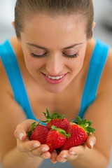 Portrait of young woman enjoying strawberries