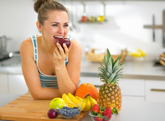 Young woman eating apple in kitchen