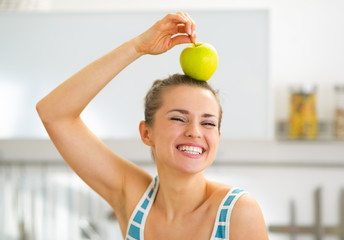 Portrait of happy young woman holding apple on head