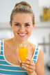 Portrait of happy young woman with glass of fresh orange juice