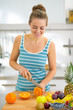 Happy young woman cutting orange