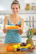 Happy young woman showing plate with orange slices
