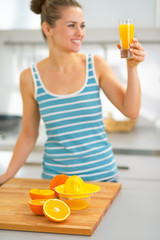 Closeup on oranges on table and woman with glass of fresh juice
