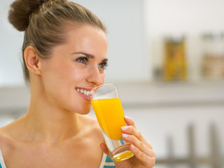 Portrait of happy young woman drinking fresh orange juice