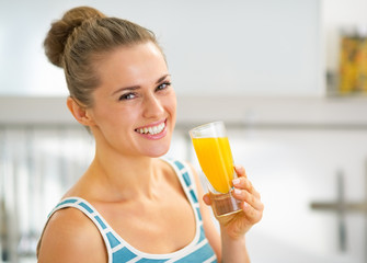 Portrait of smiling young woman with glass of fresh orange juice