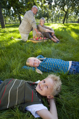 Brother and sister (9-13) lying on grass, parents in background, smiling, portrait