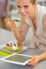 Happy young woman eating fruit salad and using tablet pc