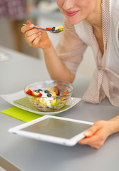 Closeup on happy woman eating fruit salad and using tablet pc