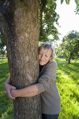 Mature woman embracing tree, eyes closed