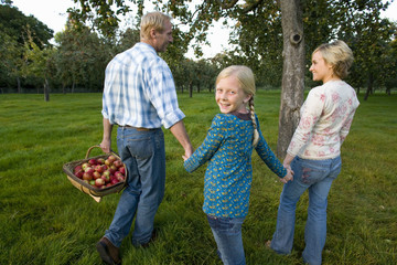 Girl (11-13) holding hands with parents, father with basket of apples, smiling, portrait