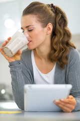 Young woman drinking smoothie and using tablet pc