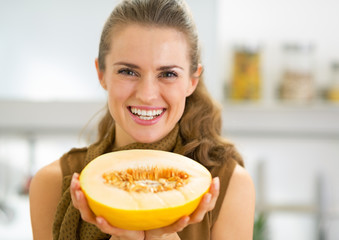 Happy young woman showing melon slice