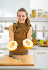 Smiling young woman showing melon slices in kitchen