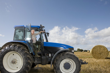 Farmer stepping down from tractor in hay field