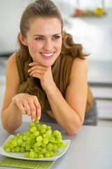 Happy young woman eating grape in kitchen
