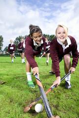 Portrait of smiling teenage girls playing field hockey