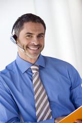 Businessman wearing telephone headset, smiling, portrait (tilt)