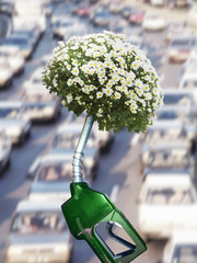 Green gas pump with blooming plant at end of nozzle and traffic in background