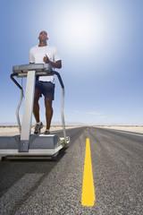 Man running on treadmill on remote desert road