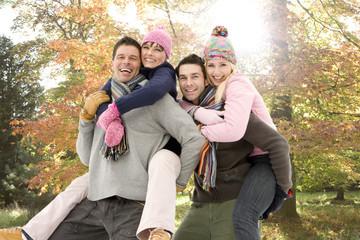 Portrait of men piggybacking women in park