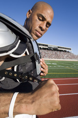 Football player putting pads on