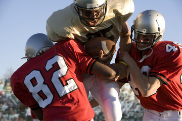 Defenders tackling running back carrying football