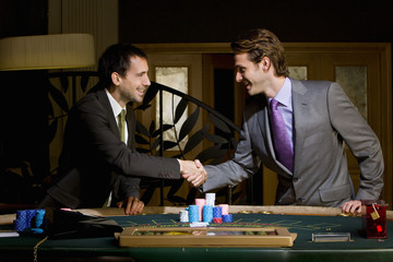 Two young men shaking hands over poker table, smiling, side view