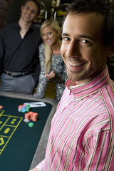 Young man by friends gambling at roulette table, smiling, portrait, close-up