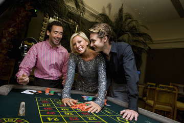 Young woman and friends gambling at roulette table, hands on chips, smiling, portrait