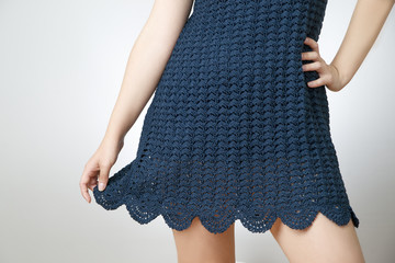 Young woman in a short skirt knitted on a gray background