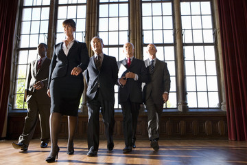 Businesswoman leading small group of businessmen in hall, low angle view