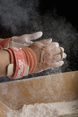 Male gymnast powdering hands, close-up of hands