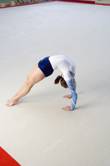 Female gymnast performing backbend, elevated view