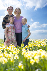 Family standing in field of daffodils