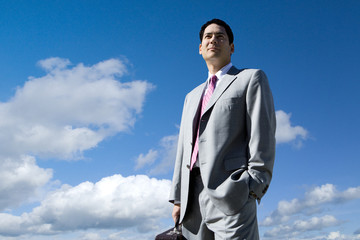 Businessman standing against blue sky