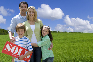Young family standing in field with sold sign