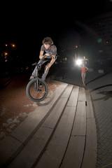 """BMX rider performing air trick """"bunny hop-180-barspin"""""""