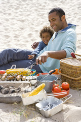 Father with son preparing barbecue on beach