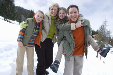 Portrait of young happy family standing in snow