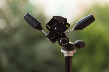 closeup of tripod camera head with bokeh background