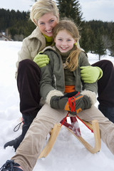 Portrait of mother and daughter on snow sled