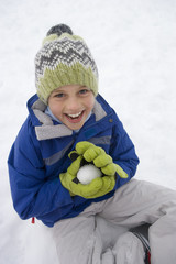 Portrait of young boy making snowball