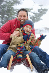 Father and son snow sledding