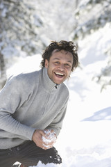Portrait of mature mixed race man with snowball