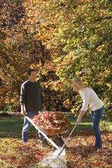 Couple doing yard work in autumn