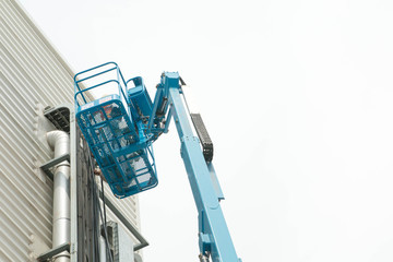 Hydraulic mobile construction platform elevated towards a blue