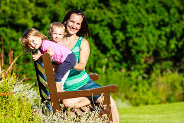 Junge Mutter sitzt mit zwei kleinen Mädchen auf einer Parkbank